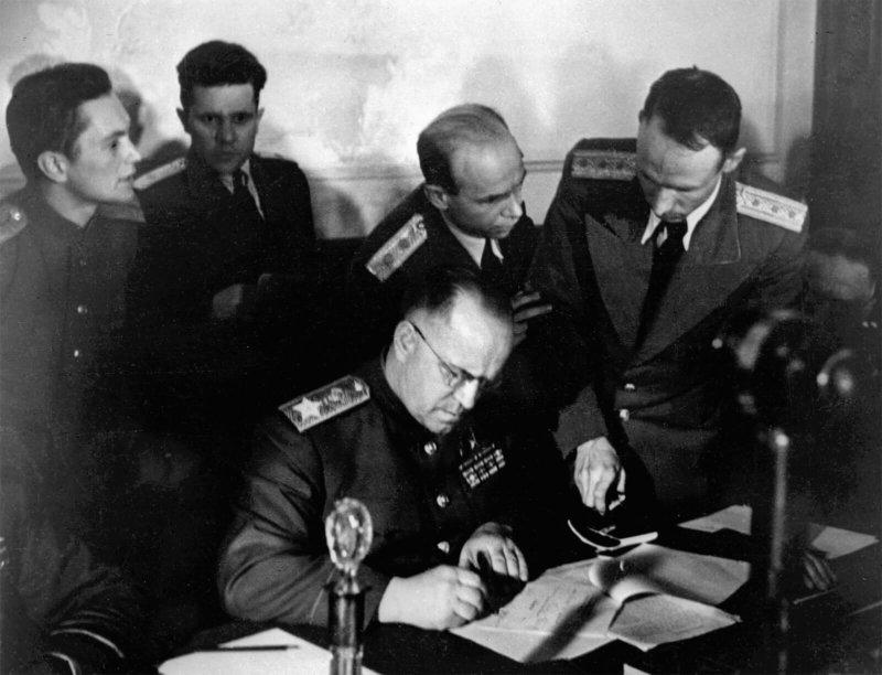 Маршал Советского Союза Георгий Константинович Жуков (в центре) подписывает Акт о безоговорочной капитуляции фашисткой Германии в Карлсхорсте в Берлине