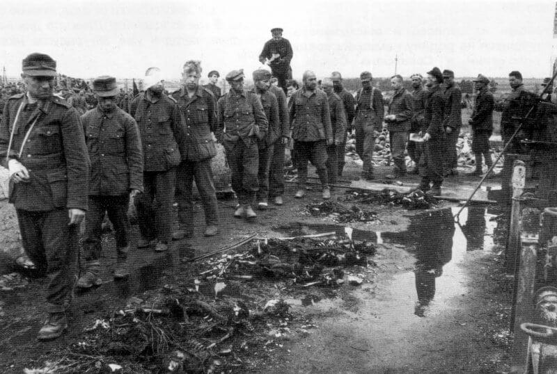 Немецких военнопленных проводят по концлагерю Майданек. На земле лежат останки узников лагеря смерти. Окраина Люблина. Польша